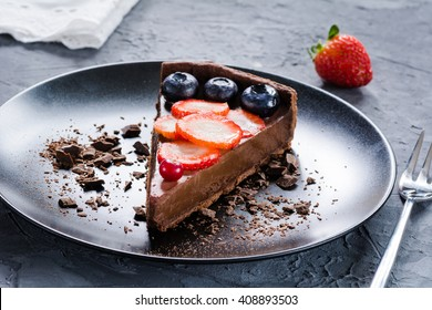 Delicious chocolate mousse pie on a plate decorated with fresh strawberries, blueberries and cranberries. Selective focus