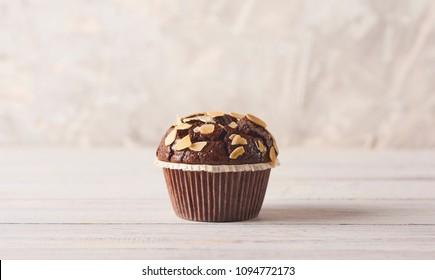 Delicious chocolate muffin on white concrete background. Minimal concept