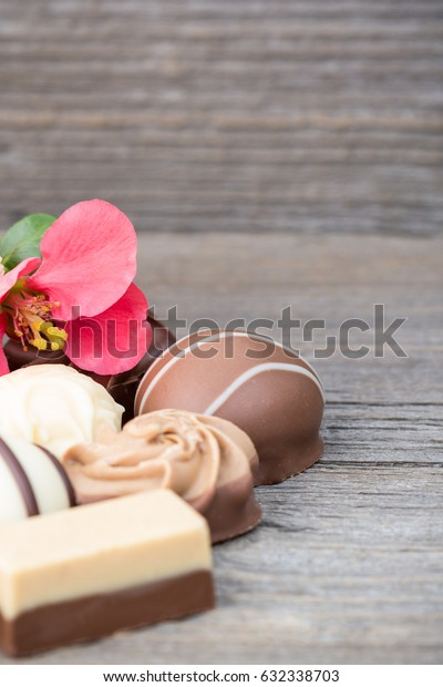 Delicious chocolate pralines on wooden background
