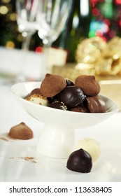 Delicious chocolate pralines and truffles on Christmass tree background