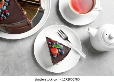 Delicious chocolate sponge berry cake and tea set on grey background, top view