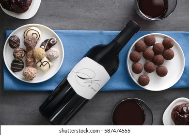 Delicious chocolate sweets and red wine on grey background
