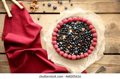 Delicious chocolate tart with berries on wooden background
