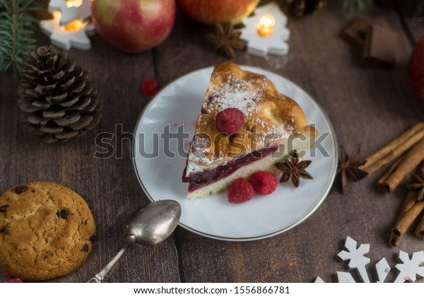 Delicious Christmas raspberry pie with berry filling and icing sugar and spices on a dark background.