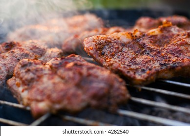 Delicious chuck steaks on the grill. Shallow depth of field.
