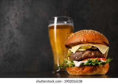 Köstlicher klassischer Burger mit Cutlet und Glas kaltes Bier auf Steinhintergrund. Schädliches und schnelles Essen.