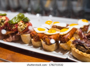 Delicious close up of pintxos/pinchos from San Sebastian (Donostia, Basque Autonomous community, Spain). Typical meal, kind of like spanish tapas. Porc, eggs and a special sauce on some bread.