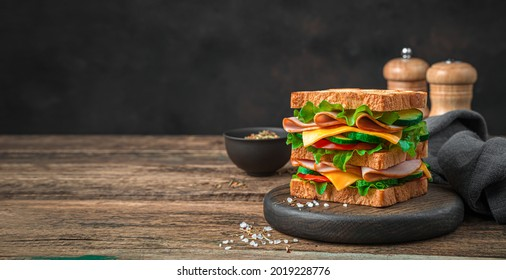Delicious club sandwich with vegetables, ham, cheese and fried toast on a brown background. Side view, copy space.