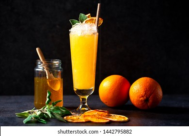 Delicious cocktail paired with jar of honey, green leaves and two oranges on dark background