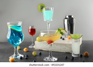 Delicious cocktails with sweet berries on gray table