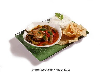 Delicious Coconut Milk Fish Head curry  served with plain rice and poppadom on the banana leaf plate isolated on white background