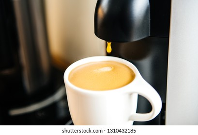 Delicious coffee pouring from the caffe espresso machine in the white luxury porcelain cup - drop by drop of the hot coffee