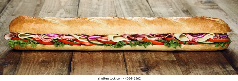 Delicious cold meat and salad French baguette with lettuce, tomato and onion trimmings served whole on a rustic wooden table in a wide angle panoramic banner format
