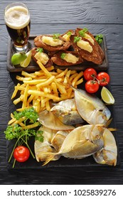 delicious cold smoked fish and french fries served on a black slate tray with capelin caviar toasts and glass of beer, vertical view from above