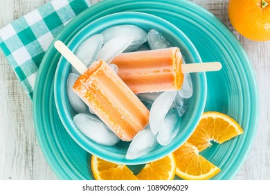 Delicious cold summer treat of tangerine popsicles and oranges in a blue bowl with ice