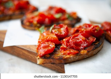 Delicious and colorful Bruschetta made with grilled cherry tomatoes on top of toasted bread rubbed with garlic, dressed with basil, olive oil and salt on a wooden board. Natural light.