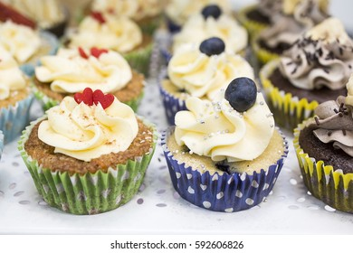 Delicious colorful cupcakes with buttercream and fruits