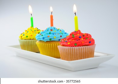 Delicious colorful cupcakes with lit candles.