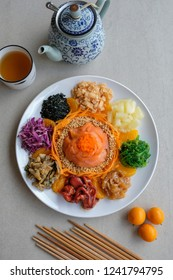 Delicious and colorful display of Chinese prosperity cuisine / Yee Sang aka Prosperity Toss / Carrot strips, purple cabbage, fresh seaweeds, jelly fish, deep fried fish skin, ground peanuts, fritters