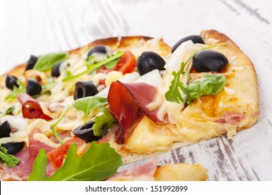 Delicious colorful pizza with tomatoes, melted cheese, black olives, onions, ham and fresh herbs on white wooden background. Culinary mediterranean pizza eating.