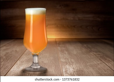 Delicious colorful unfiltered hazy IPA pale ale craft beer in tulip glass on wood table, with copy space