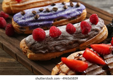 Delicious colourful eclairs with berries on wooden cutting board