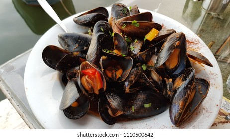 Delicious cooked mussels with red pepper on white plate. Black shell mussels closeup. Mediterranean seafood dish. Greek cuisine