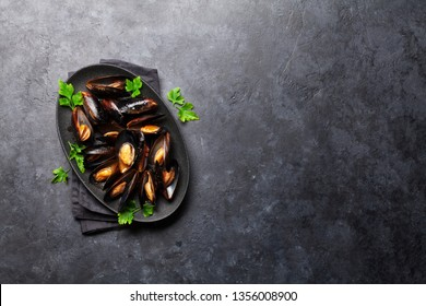 Delicious cooked seafood mussels with tomato sauce, parsley and lemon. Top view with space for your text