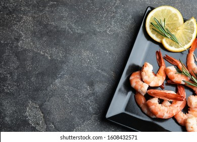 Delicious cooked shrimps with rosemary and lemon on grey table, top view. Space for text