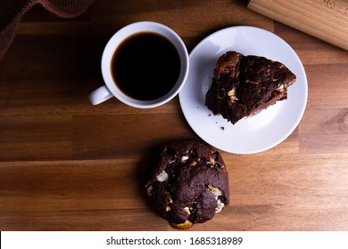Delicious cookie cakes with chocolate with a cup of coffee on a wooden board with copy space