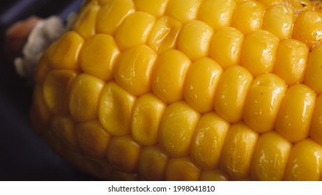 Delicious corn on the cob captured in an extreme close up. The brightly glowing yellow kernels form a recognizable pattern. The cob was buttered up, and fried in an iron cast skillet.