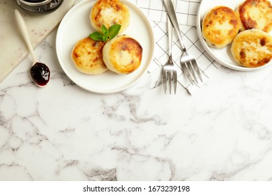 Delicious cottage cheese pancakes on white marble table, flat lay. Space for text