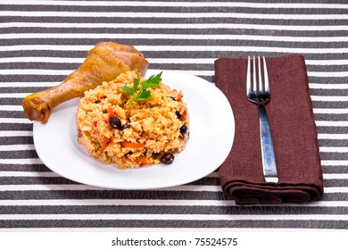 delicious couscous with chicken on a striped background