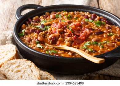 Delicious cowboy stew of beans with ground beef, bacon in a spicy sauce closeup in a bowl on the table. horizontal