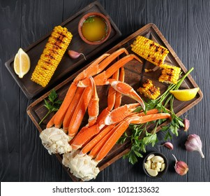 delicious Crab legs served with melted butter, garlic cloves, lemon slices, grilled corn in cobs and fresh parsley on old wooden cutting board, view from above