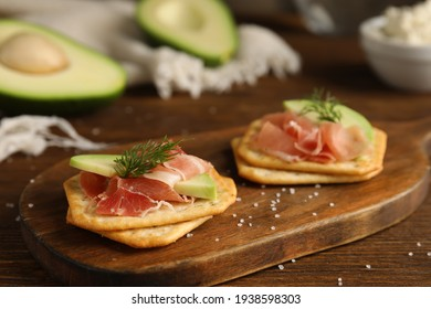 Delicious crackers with avocado, prosciutto and dill on wooden table, closeup