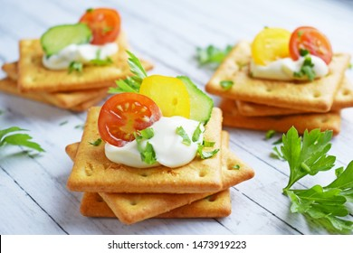 Delicious crackers with cheese sauce and vegetables.Snack on wooden background.
