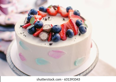 Delicious cream cake with chocolate balls decorated with strawberries and blueberries