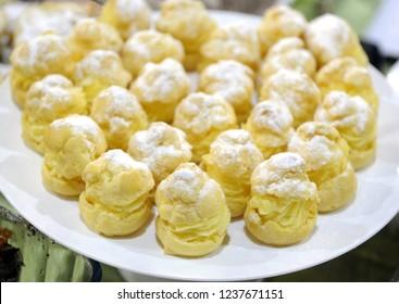 Delicious cream puff cakes with cream and powdered sugar
