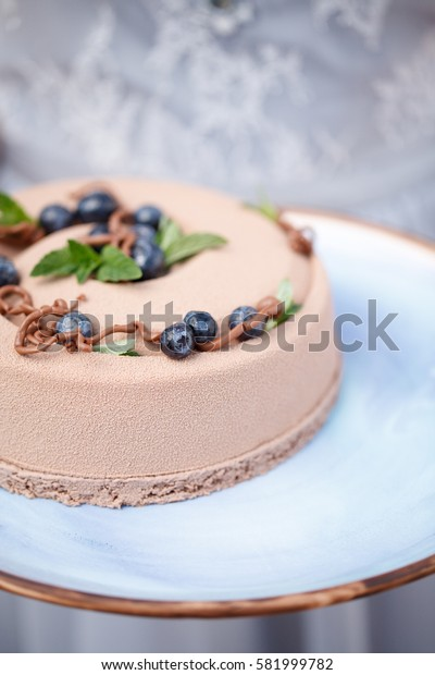 delicious creamy brown cake closeup on blue plate
