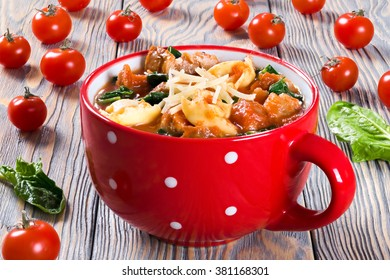 Delicious creamy tomato soup with tortellini, Italian sausages, spinach, decorated with parmesan cheese in a red mug on a table, close-up, selective focus