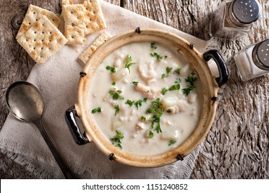 A delicious creamy white fish chowder with haddock, cod, potato, and onion garnished with parsley and served with soda crackers.