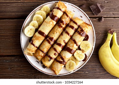 Delicious crepe roll with banana slices on wooden background. Top view, flat lay