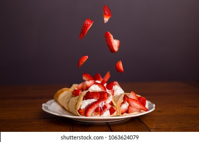 Delicious crepes filled with strawberries and whipped cream with strawberries falling on top of the crepes.
