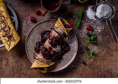 Delicious crepes with forest fruit, topped and filled with forest fruit, mint and dark chocolate, delicious breakfast