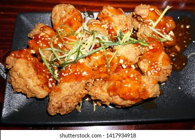 Delicious crispy deep fried spicy seasoning battered chicken honey soy sauce chopped peanut with sweet chillies sauce on black clay plate Korean food Asian cuisine