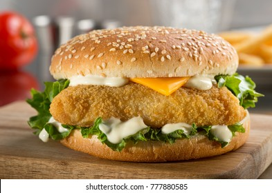 A delicious crispy fish burger with cheese, lettuce, and mayonnaise.