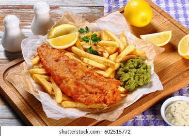 delicious crispy fish and chips - fried cod, french fries, lemon slices, tartar sauce and mushy peas on plate on paper. parsley and lemon wedges on wooden table, view from above, close-up