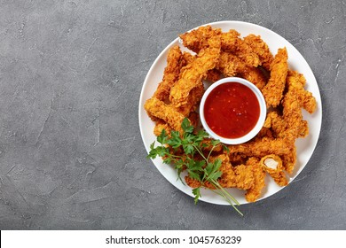 delicious crispy fried chicken breast strips  with tomato sauce on white plate, on concrete table, view from above