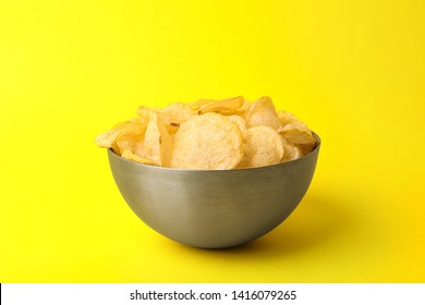Delicious crispy potato chips in bowl on color background
